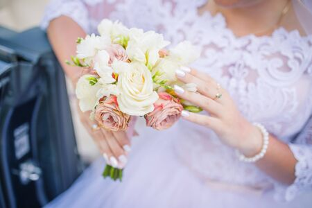 blurred background wedding theme. brides bouquet and hands closeup. Wedding day. Stock Photo