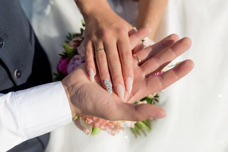 Picture of man and woman with wedding ring.Young married couple holding hands, ceremony wedding day. Newly wed couples hands with wedding rings