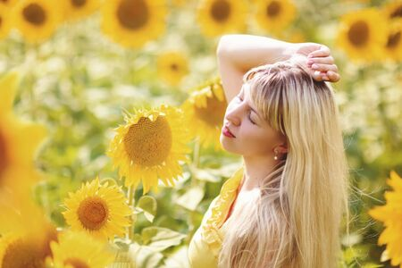 Beautiful young girl enjoying nature on the field of sunflowers at sunset Stok Fotoğraf