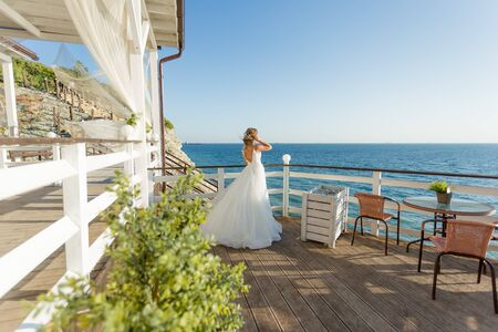 Lovely bride in white wedding dress posing near the sea with beautiful background Stok Fotoğraf