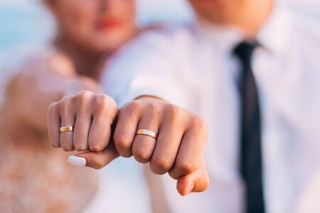 Newly married couple holding closed fists with wedding rings.