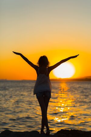 strong confidence woman open arms under the sunrise at seaside. Stok Fotoğraf