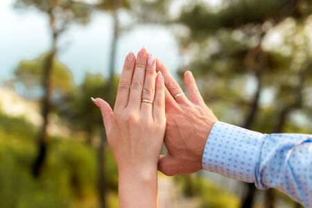 Wedding rings in the hands of the bride and groom on the sea background.