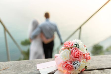 Wedding bouquet on wedding couple background, stay at the beach.