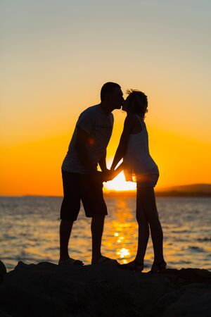 young couple kissing at sunset on beach.