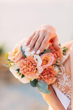 Beautiful wedding bouquet of flowers in hands of the bride.