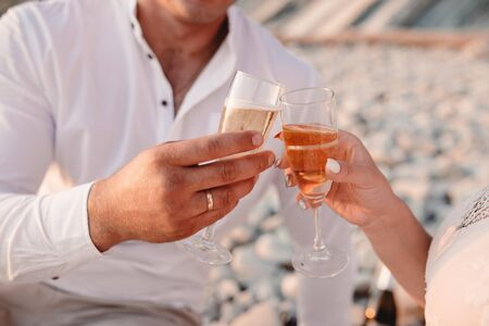 Man and woman clanging wine glasses with champagne at sunset. Фото со стока