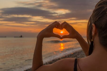 Silhouette hand in heart shape with sunrise in the middle and beach background.