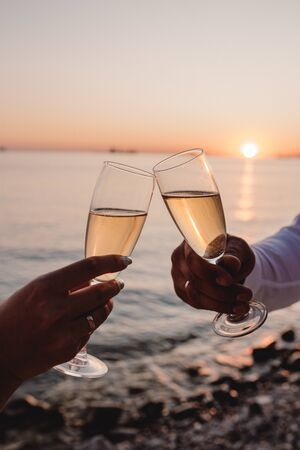 Man and woman clanging wine glasses with champagne at sunset dramatic sky background Фото со стока