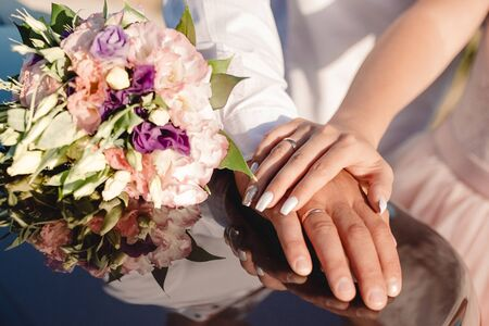 Hands of bride and groom with rings near wedding bouquet. Marriage concept.