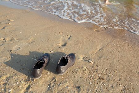 Work Life Balance Concept, Businessman take off his Working Shoes and leave it on the Sand Beach for Walk into the Sea on Sunny Day. Top View.