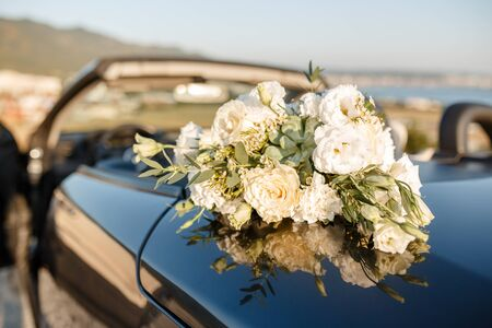 Beautiful big bouquet of a bride on a wedding from top lying in a convertible.
