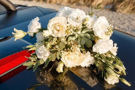 wedding rings lie on a beautiful bouquet as bridal accessories.