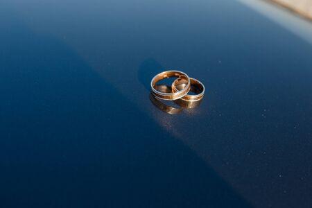 Wedding rings lie on a dark mirror background . Close up.