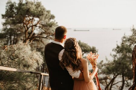 Young newly wed couple, bride and groom hugging on perfect view of mountains and sea, blue sky Zdjęcie Seryjne