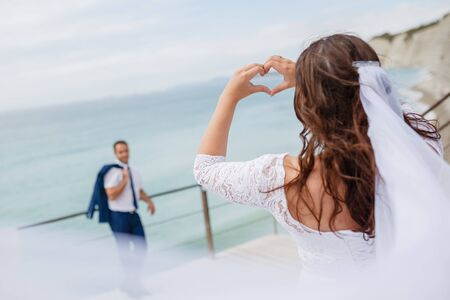 beautiful photo of a bridge making heart shapes with their hands and see on the groom.