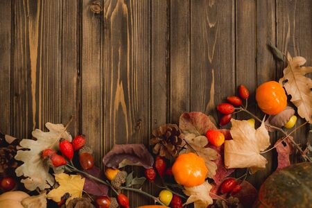 autumn background with colored leaves and pumpkins on wooden board. Reklamní fotografie