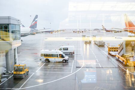 Busy airport view with airplanes and service vehicles. Travel and industry concepts.