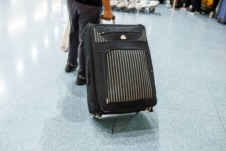 Close up of legs of man going into the airport with suitcase.