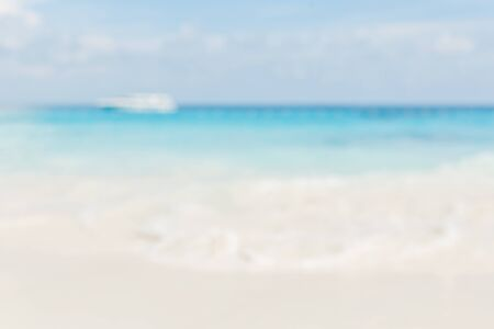 Blur summer white sand beach with sparkling sea water.