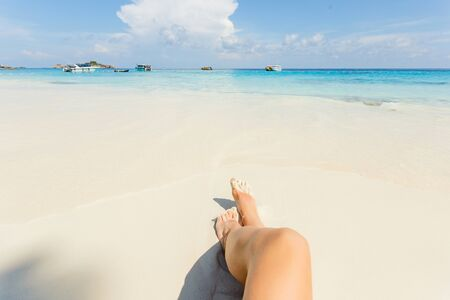 Woman tanned legs on sand beach. Travel concept. Happy feet in tropical paradise.