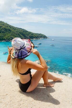 Young female sitting on viewpoint sailing rock in similan island. Freedom traveler woman enjoy a wonderful nature on top mountain with perfect view. travel concept.