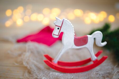 Closeup of beautiful New Year tree decorations, wooden horse against the background of Christmas lights.