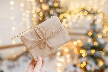 Christmas gift box with festive bokeh lighting, blurred holiday background. New year background