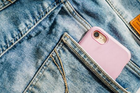 Modern smartphone in the pocket of jeans, close-up, Cell phone in the pocket of jeans in blue jeans, denim background texture