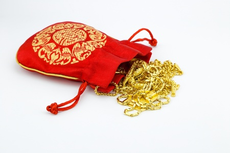 gold ornament and red bag on white background