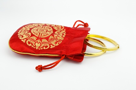 high priced: golden bracelets and red bag isolate on white background