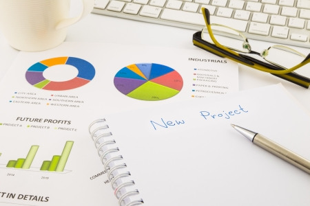 assignation: create ideas for new project, graph and chart with blank paper on office table, business concept Stock Photo