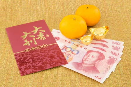 asian culture: chinese new year with decoration, money yuan banknote, ingot and orange, celebrate chinese new year festival and asian culture