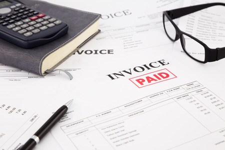 close-up picture of invoices with red paid stamp, paperwork at office