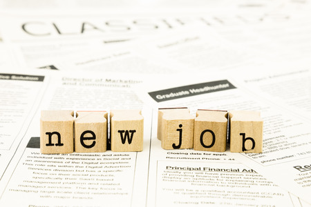 closeup new job wording on classifieds ads and newspaper, recruitment and employment concepts and ideas