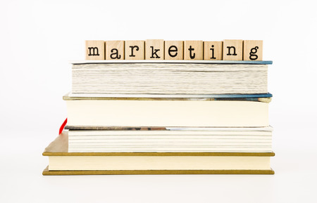 consumerism: closeup marketing wording stack on books, business and consumerism concept and ideas