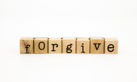condone: closeup forgive wording isolate on white background, ethic and merit concept and idea Stock Photo