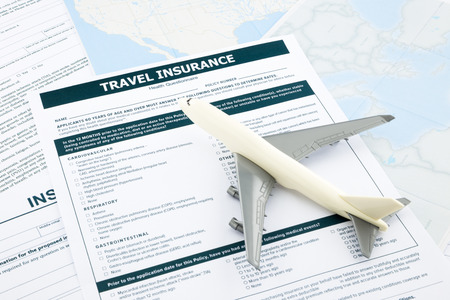travel insurance form and   plane model on world map paperwork, concept and idea for insurance business