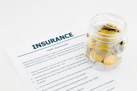 insurance health questionnaire and coins on white background