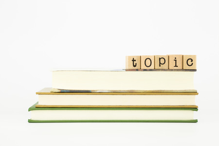 gist: topic word on wood stamps stack on books Stock Photo