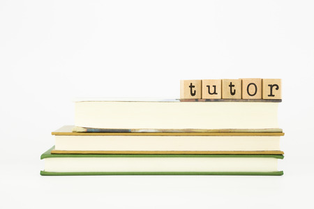 tutor word on wood stamps stack on books Stok Fotoğraf