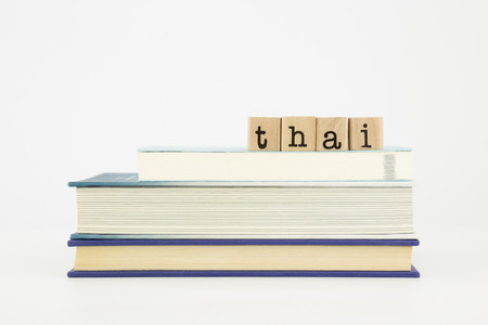 thai language: thai word on wood stamps stack on books, language and study concept