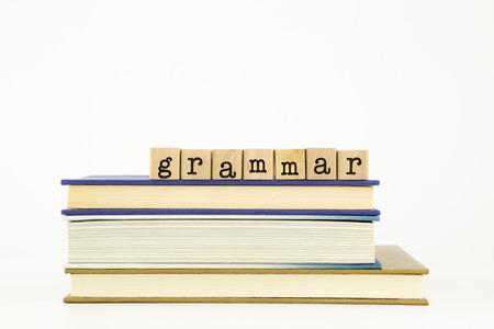 書籍、上の木製スタンプ スタック上文法単語言語と教育のコンセプト 写真素材