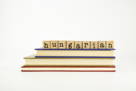 magyar: hungarian word on wood stamps stack on books, language and conversation concept Stock Photo