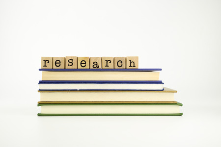 essay: research word on wood stamps stack on books, library and education concept Stock Photo