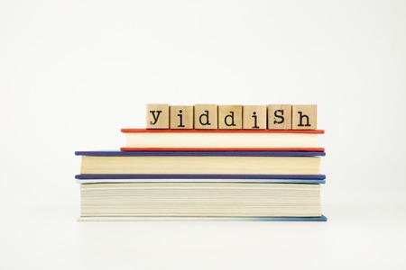 yiddish: parola yiddish sui francobolli di legno pila su libri, lingua straniera e il concetto di traduzione Archivio Fotografico