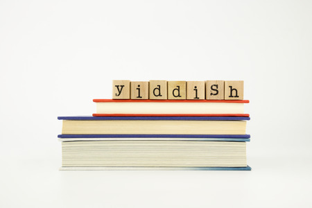 yiddish word on wood stamps stack on books, foreign language and translation concept photo