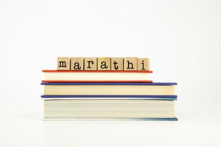 marathi: marathi word on wood stamps stack on books, foreign language and translation concept