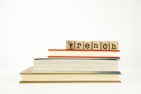french word on wood stamps stack on books, conversation and translation concept photo