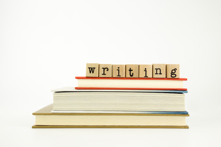 article writing: writing word on wood stamps stack on books, study and academic concept
